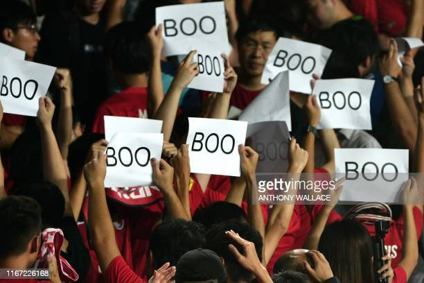 People turn their back and boo while holding up placards during the Chinese anthem at the start of the Qatar 2022 World Cup qualifying football match...