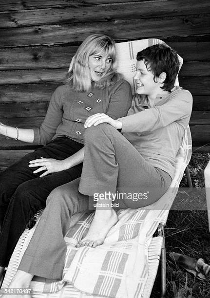 people two young girls sitting side by side talking pullover trousers aged 18 to 25 years Monika Kriemhild