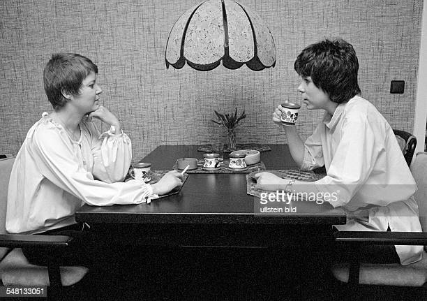 people two young women sitting at the table drinking coffee and smoking a cigarette coffee klatch blouse aged 23 to 30 years Monika Gaby Gabi