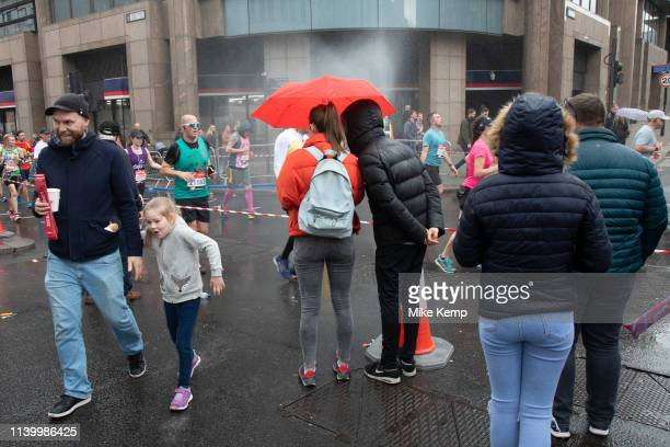 People under a red umbrella watching participants taking part in the London Marathon on 28th April 2019 in London England United Kingdom The London...
