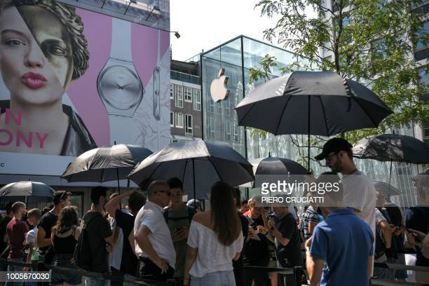 People under umbrellas protect from the sun as they queue before the opening at a new Apple Store Liberty the first Italian flagship store of Apple...