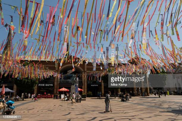 People underneath colourful bunting hanging in Broadgate near the Godiva statue in the UK City of Culture 2021 on 23rd June 2021 in Coventry, United...