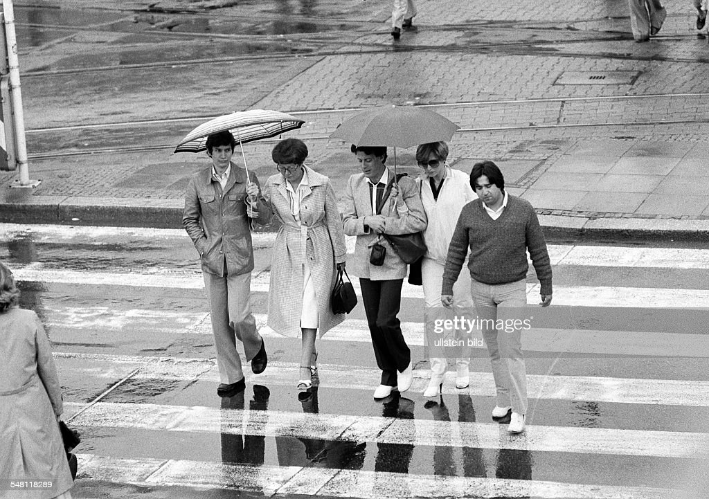 people undertake a walk in the rain, umbrellas, man, aged 30 to 40 years, women, aged 20 to 30 years, aged 50 to 60 years, boy, aged 17 to 20 years - 15.07.1980 : News Photo