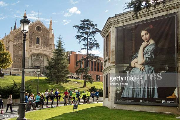 People undertake physical training in front of a billboard for an exhibition of Spanish painter Ingres posted near the main entrance of the Prado...