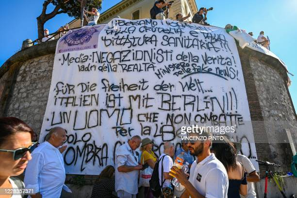 "People unfold a banner written in Italian and German as protesters from ""No Mask"" movements, Covid deniers movements, anti-5G movements and..."
