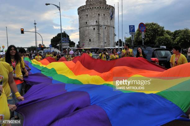 People unfurl a Peace flag as they parade in the streets of Thessaloniki northern Greece taking part in the city's 4th Gay Pride march on June 20...