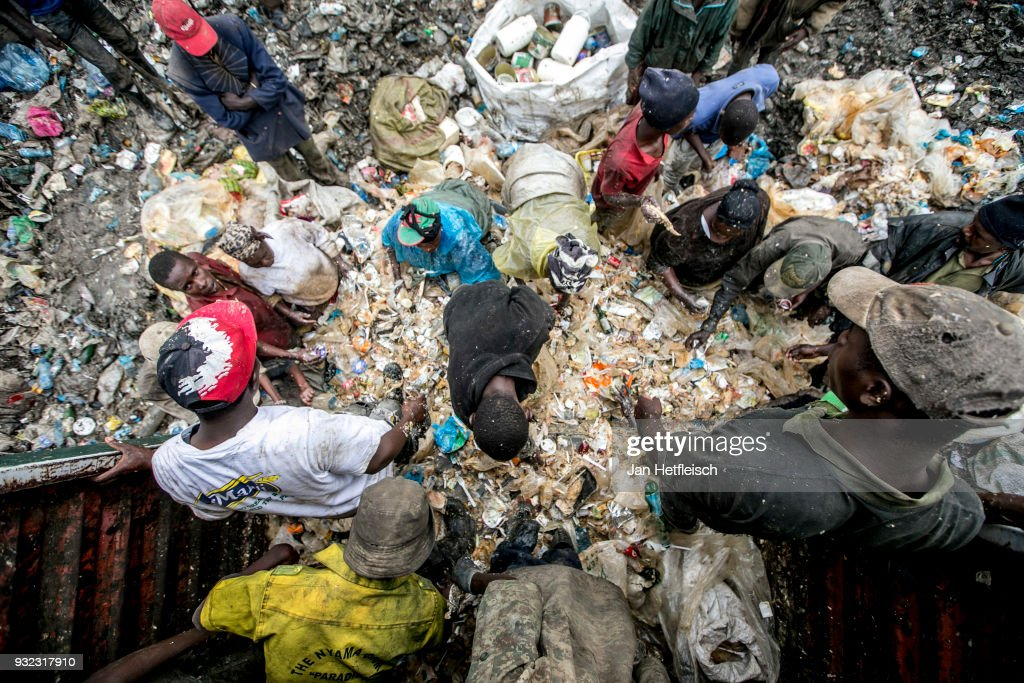 People unload a truck and look for something to eat at the Dandora Rubbish dump on March 14, 2018 in Nairobi, Kenya. The Dandora landfield is located 8 Kilometer east of the city center of Nairobi, the capital of Kenya. Every day, more than 2.000 metric tonnes of waste are dumped on this site. More than 3000 pickers work day by day at the sprawling 30-acre rubbish dump.