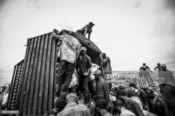People unload a truck and look for something to eat at the Dandora Rubbish dump on March 14 2018 in Nairobi Kenya The Dandora landfield is located 8...