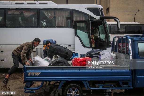 People unload luggage from a bus after the third convoy transporting the Syrian opposition fighters and their families from the rebel held areas of...
