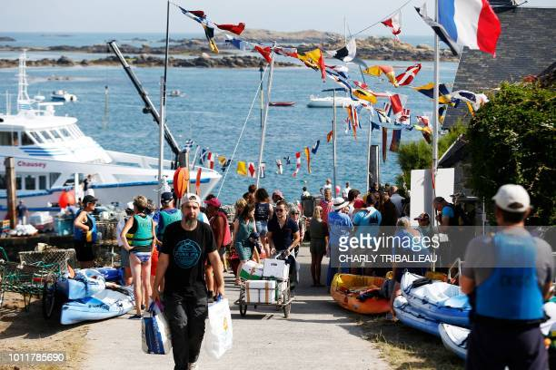 People unload the goods from the ferry boat on the Island of Chausey off the coastal town of Granville northwestern France on August 4 2018