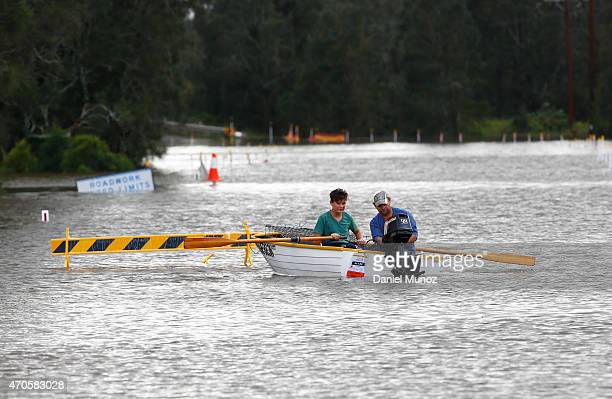 People use a boat on a flooded road on April 22 2015 near Dungog Australia Three people have died and more than 200000 are still without power as...