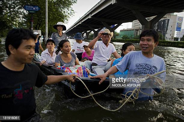 People use a boat to cross floodwaters in the Lat Phrao shopping and business district in Bangkok on November 8, 2011. Thailand's prime minister said...