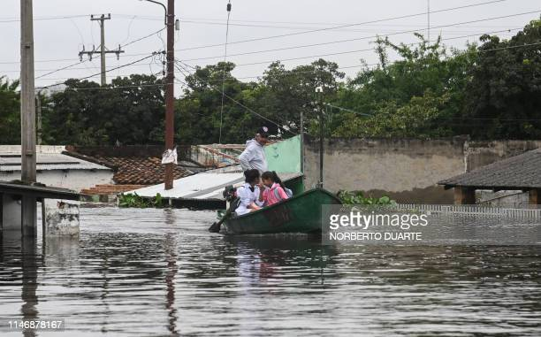 People use a boat to move around a flooded neighbourhood in Asuncion on May 29 after heavy rains in the past weeks caused the overflowing of the...