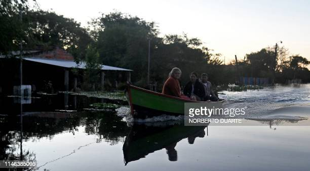 TOPSHOT People use a boat to move around the flooded town of Puerto Falcon near Asuncion on May 25 after heavy rains in the past weeks caused the...