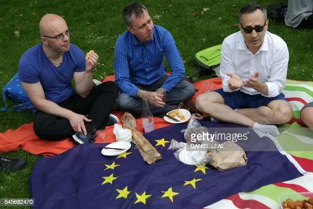 People use a European Union flag as a blanket while taking part during a picnic against Brexit organised by the General Assembly in Green Park in...