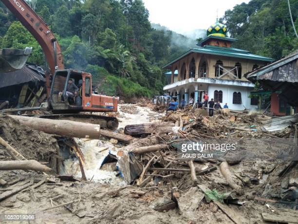 People use a heavy equipment to remove debris after flash floods hit the Saladi village in Mandailing Natal North Sumatra on October 13 2018 At least...