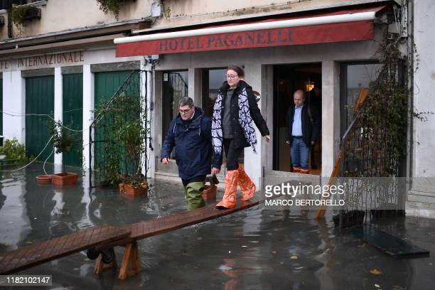 People use a makeshift footbridge to exit a flooded hotel after an exceptional overnight Alta Acqua high tide water level on November 13 2019 in...