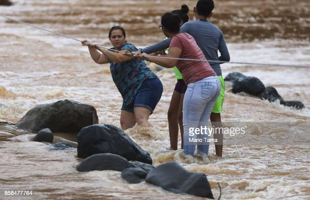 People use a rope line to cross the San Lorenzo de Morovis river more than two weeks after Hurricane Maria hit the island on October 6, 2017 in San...