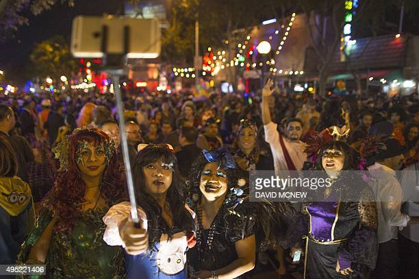 People use a selfie stick to photograph themselves at the Halloween Carnaval on October 31 2015 in West Hollywood California Carnaval officials paid...