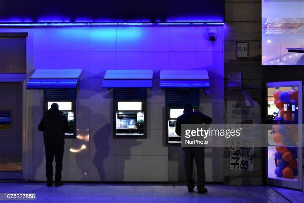 People use an ATM machine in Ankara Turkey on December 27 2018 A year is passed under economic difficulties as part of high inflation rates and the...
