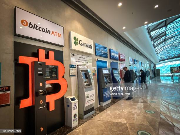 """People use bank ATM""""s next to a Bitcoin ATM machine at a shopping mall on April 16, 2021 in Istanbul, Turkey. Turkey's Central Bank announced a ban..."""