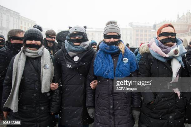 People use black bands over their eyes and mouths during a silent assembly named Stolen Justice in Krakow Stolen Justice happening intend to express...