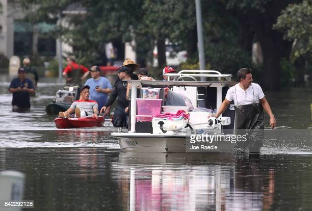 People use boats to help bring items out of homes in an area where a mandatory evacuation is still under effect after flood water inundated them...