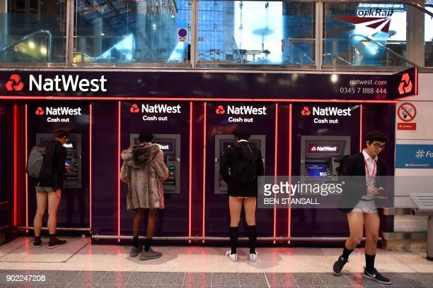 People use cash machines as they take part in the annual 'No Trousers On The Tube Day' at Liverpool Street Station in London on January 7, 2018....
