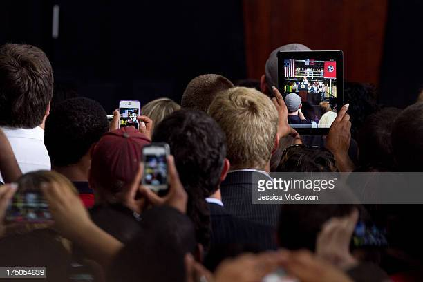 People use electronic devices to record US President Barack Obama as he makes a speech about the economy and jobs at an Amazoncom Fulfillment Center...