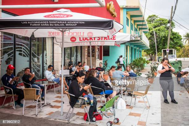 people use free wifi with smartphones in a coffee, varadero, cuba - data stream stock photos and pictures