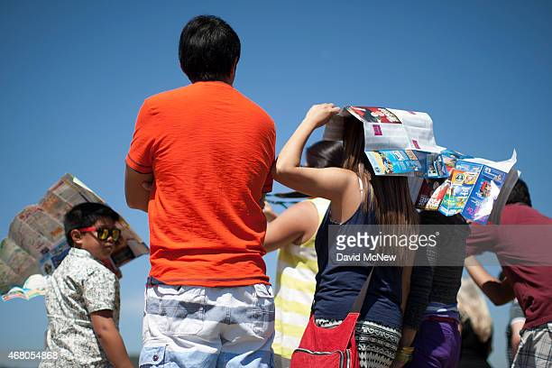 People use Hollywood tourist maps as makeshift sunshade in Griffith Park on March 29 2015 in Los Angeles California A recordbreaking series of...