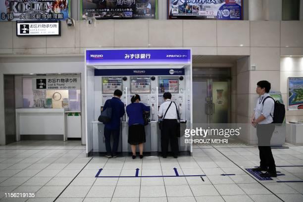 People use Mizuho bank automatic teller machines at Shinagawa train station in Tokyo on July 18, 2019.