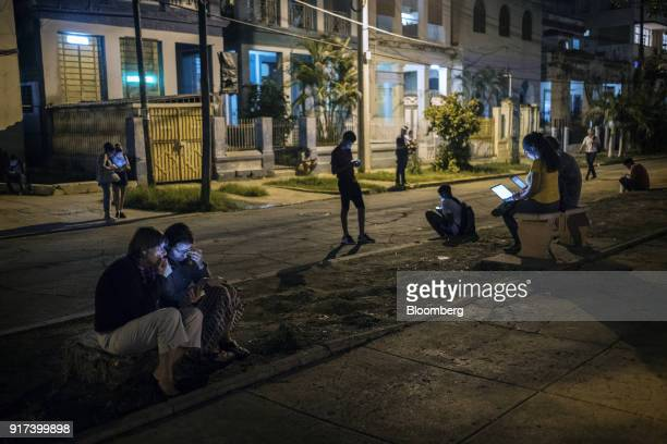 People use mobile devices and laptop commuters at a wireless communications hotspot at night in Havana Cuba on Thursday Jan 25 2018 The Information...