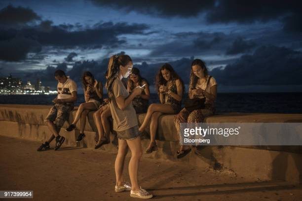 People use mobile devices at a wireless communications hotspot along the Malecon roadway at night in Havana Cuba on Tuesday Jan 30 2018 The...