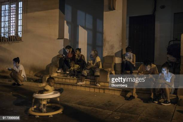 People use mobile devices at a wireless communications hotspot at night in Havana Cuba on Tuesday Jan 30 2018 The Information Technology Industry...