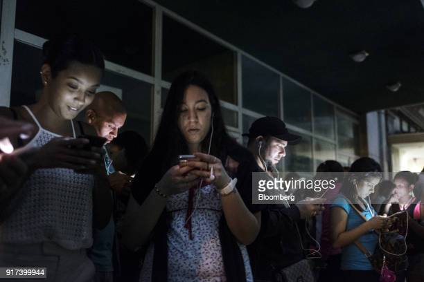 People use mobile devices at a wireless communications hotspot at night in Havana Cuba on Saturday Jan 27 2018 The Information Technology Industry...