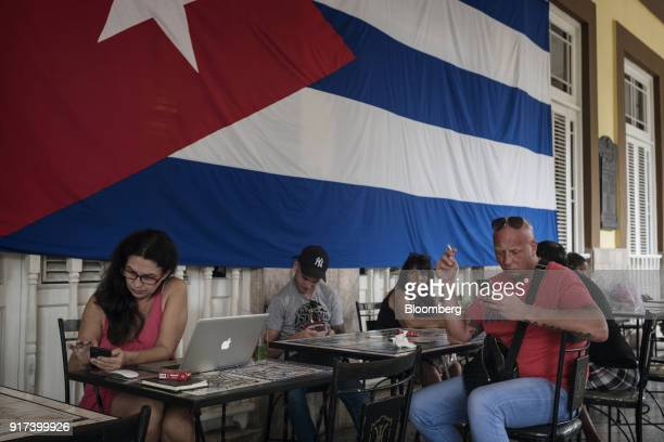 People use mobile devices at a wireless communications hotspot at the Hotel Inglaterra in Havana Cuba on Monday Jan 29 2018 The Information...