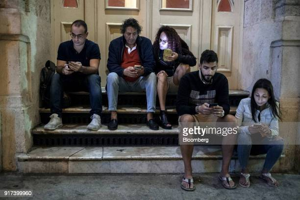 People use mobile devices at a wireless communications hotspot outside the Hotel Inglaterra in Havana Cuba on Sunday Jan 28 2018 The Information...