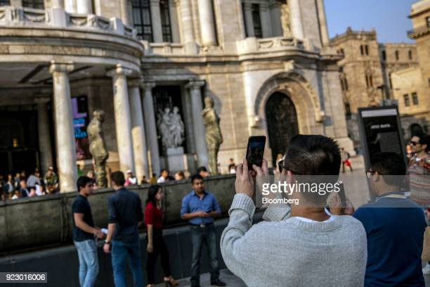 People use mobile devices to take photographs of the Palacio de Bellas Artes in Mexico City Mexico on Friday Feb 16 2018 The National Institute of...