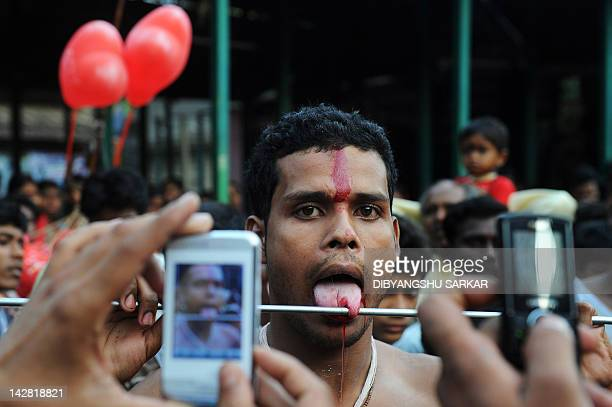 People use mobile phones to photograph an Indian Hindu devotee who has his tongue pierced with a metal rod during the ritual of Shiva Gajan at a...