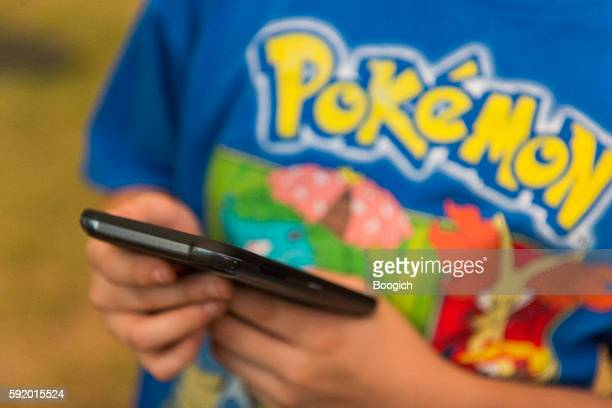 People Use Mobile Phones to Play Game Pokemon Go Outdoors