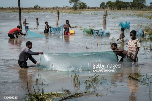 People use nets to fish in a flooded area hit by the Cyclone Idai near Tica, Mozambique, on March 24, 2019. - Cyclone Idai smashed into Mozambique's...