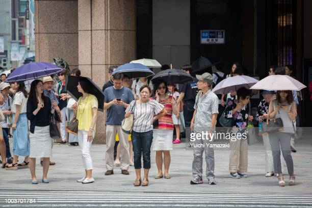 People use parasols to try and escape the heat on July 22 2018 in Ginza Tokyo Japan A deadly heatwave which has killed at least 30 people continues...