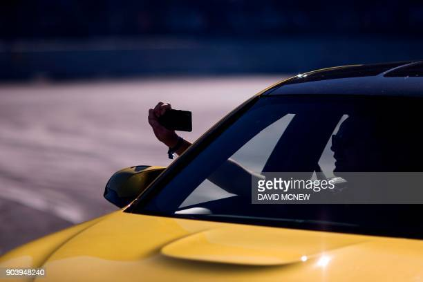 People use personal devices to record their ride with a driver drifting a car around track at the BMW Ultimate Driving Experience exhibit during CES...