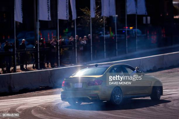 People use personal devices to record their ride with a driver drifting a car around track at the BMW Ultimate Driving Experience exhibitduring CES...