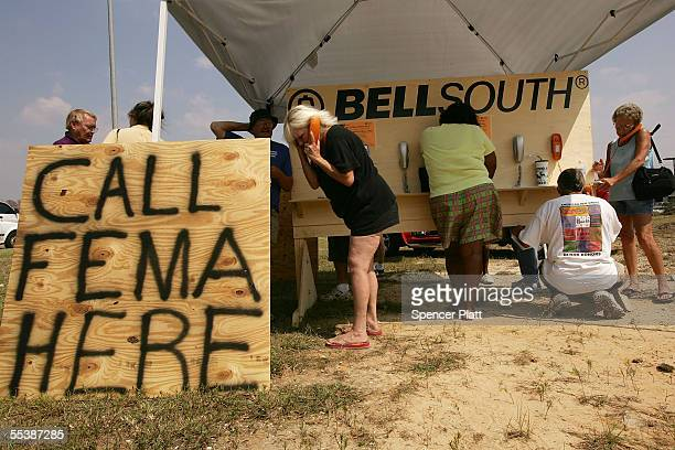 People use phones at a mobile phone center to call the Federal Emergency Management Agency September 12 2005 in Gulfport Mississippi Thousands of...
