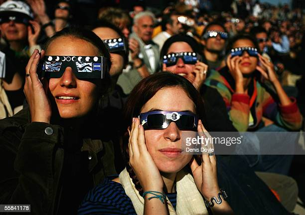 People use protective glasses to view an annular eclipse at the Planetarium on October 3 2005 in Madrid Spain An annular eclipse is where most of the...