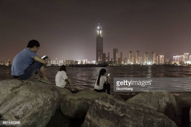 People use smartphones as buildings stand illuminated along the Yangtze River at night in Wuhan China on Tuesday June 13 2017 China's central bank...