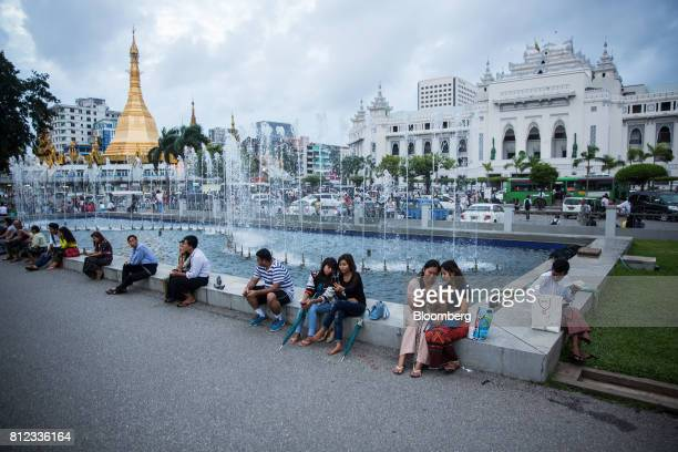 People use smartphones while sitting in front of a water fountain next to the Sule Pagoda stupa at Maha Bandula Park in Yangon Myanmar on Thursday...