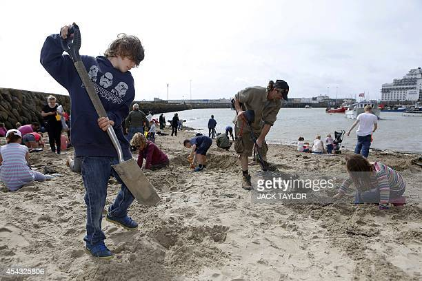 People use spades and metal detectors as they search a beach in Folkestone southeast England on August 29 2014 for gold bullion buried there by...